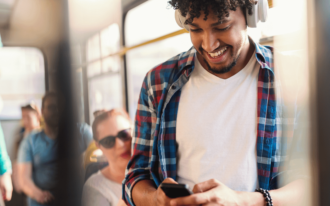 man smiling on train with his mobile phone google app campaigns