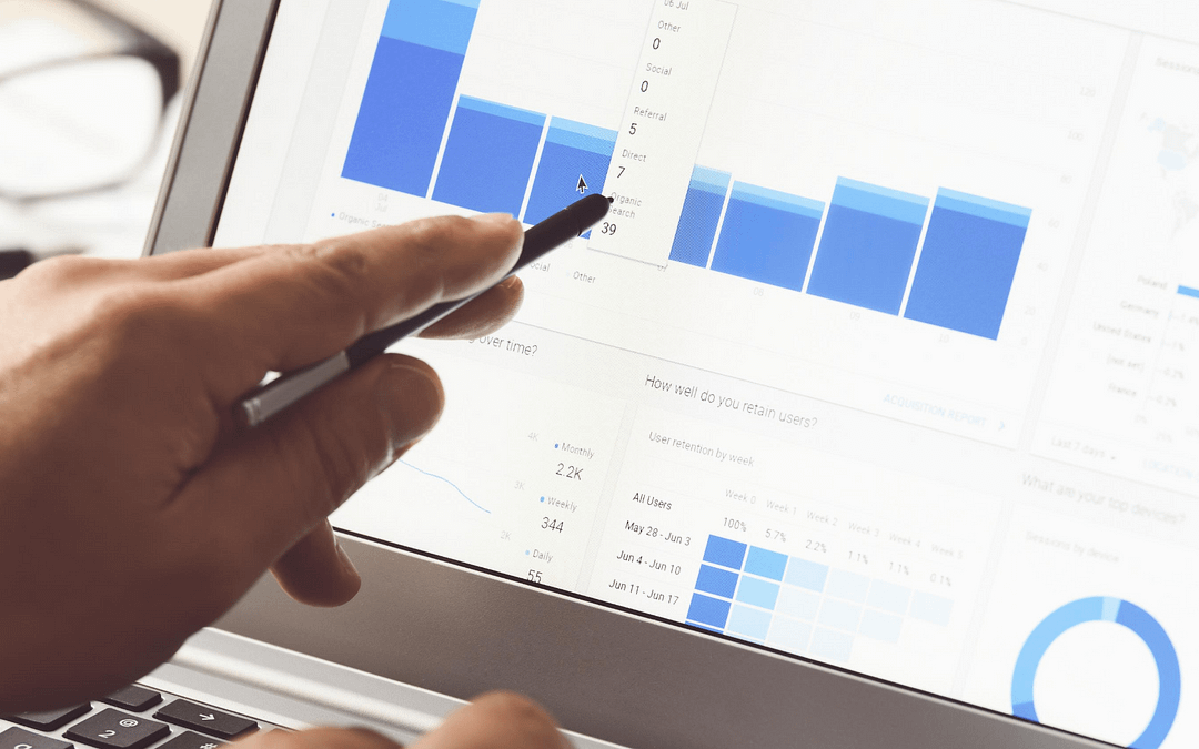 person pointing at a bar chart on a laptop